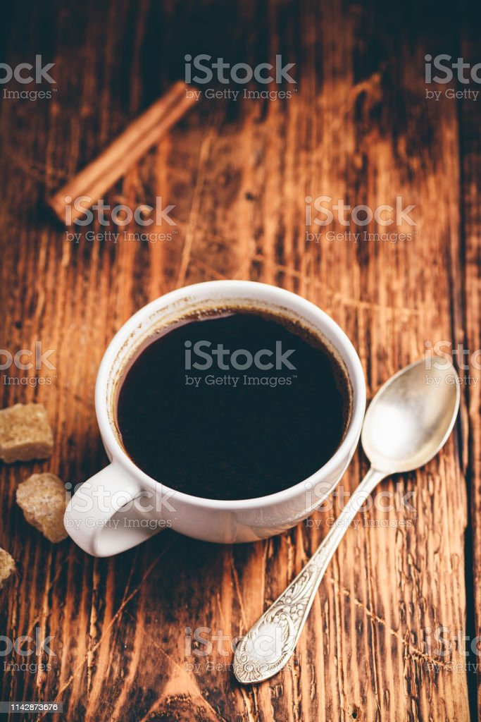 Black coffee in white cup with sugar and cinnamon sticks
