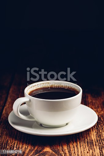 Black coffee in white cup over wooden surface
