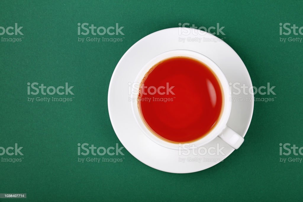 White cup of black tea on saucer over green stock photo