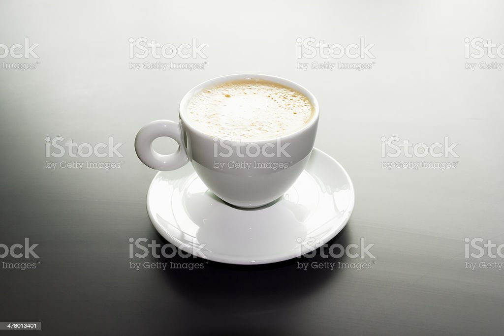 white cup of cappuccino on a black matte surface royalty-free stock photo