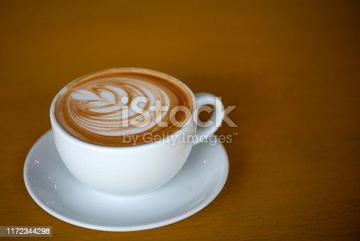 A white cup of cappuccino with latte art on brown wood table with low light.