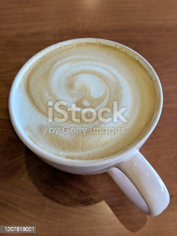 White cup of Cappuccino with swirl in foam on saucer on table.