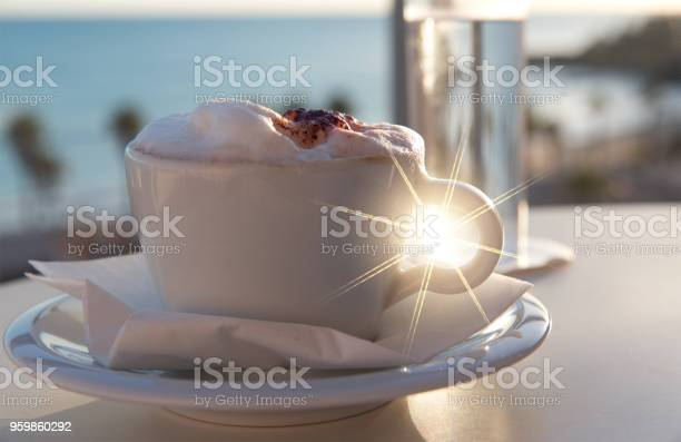 White cup of coffee and glass of water on sea beach and palms  At Sunset Or Sunrise Beach, holiday concept