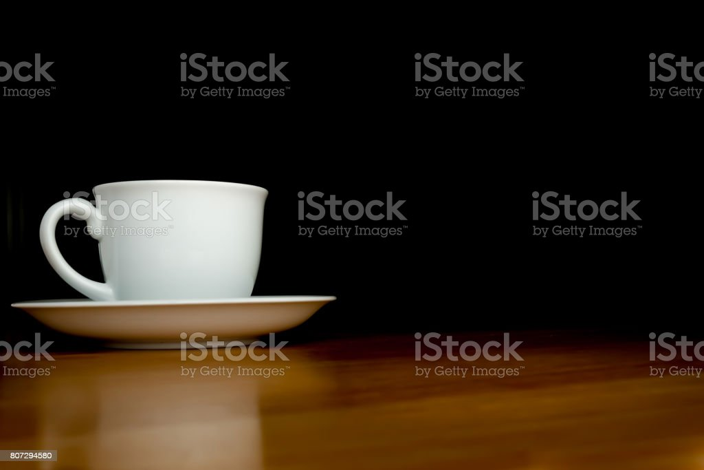 A white cup of coffee in the dark background on wood table. stock photo