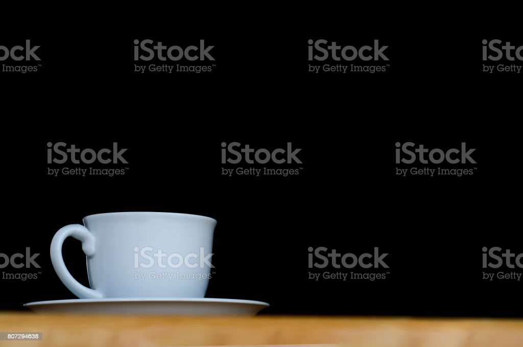 A white cup of coffee in the dark background. stock photo