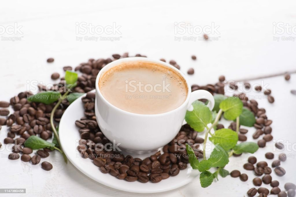 white cup of coffee on a background of scattered coffee beans on a...
