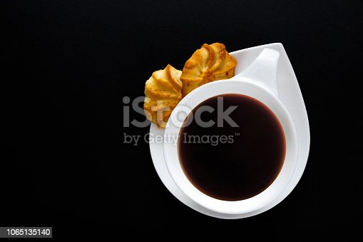 1009835562 istock photo White cup of coffee on a black background close-up with copy space for text in minimalism style. Flat lay top view 1065135140