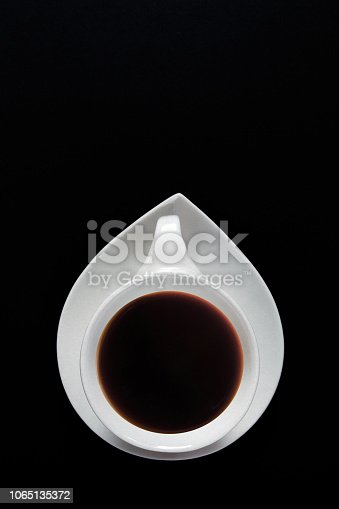 1009835562 istock photo White cup of coffee on a black background close-up with copy space for text in minimalism style. Flat lay top view 1065135372