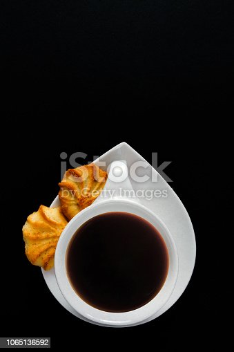1009835562 istock photo White cup of coffee on a black background close-up with copy space for text in minimalism style. Flat lay top view 1065136592