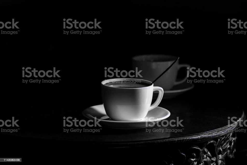 White cup of black coffee on black background - black and white...