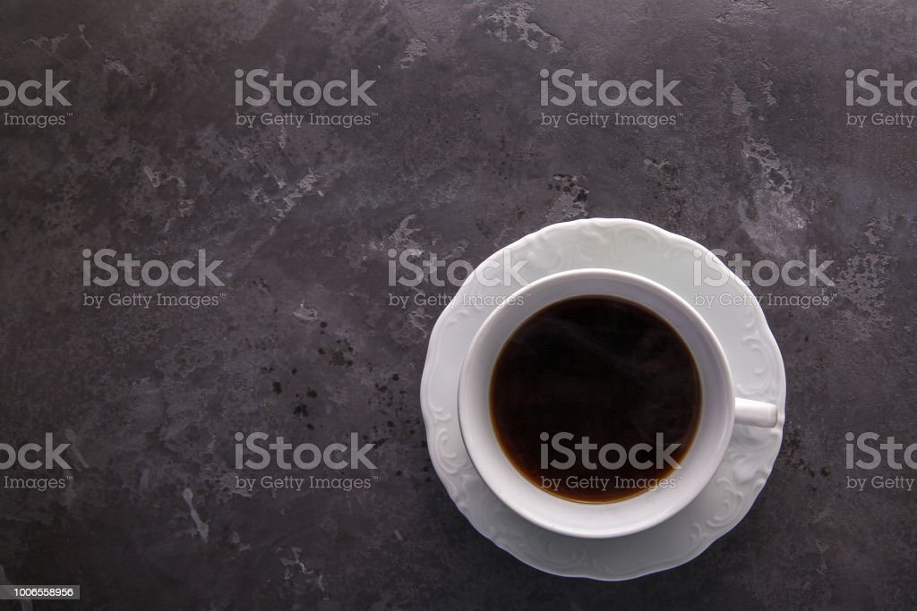 White cup of coffee on dark grey beton background decorated with coffee beans. stock photo