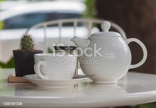 istock White cup of coffee or tea on white table with little cactus 1033197208