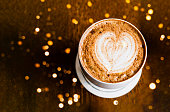 White cup of coffee with crema on wooden background with blur effect. Close up, copy space