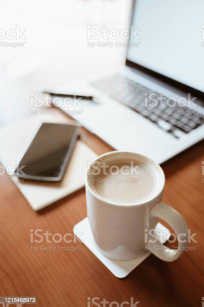 Photo of White cup of coffee with laptop and smart phone on wooden office desk