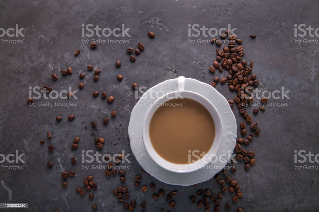 White cup of coffee with milk or tea with milk on dark grey beton background decorated with coffee beans. stock photo