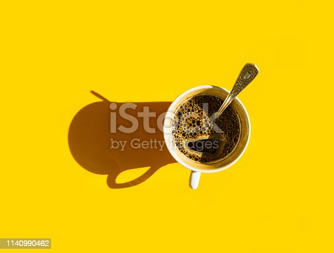 White cup of freshly brewed coffee with foamy crema tea spoon on solid yellow background. Top view. Morning breakfast energy fashion business concept. Harsh light hard ling shadow