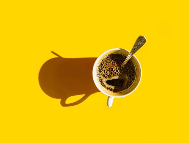 Weiße Tasse frisch gebrühter Kaffee mit schaumigem crema-Tee-Löffel auf solidem gelbem Hintergrund. Top View. Morgens Frühstück Energie-Mode Mode Business-Konzept. Hartes, leicht harter, schwerer Schatten. Vorlage – Foto