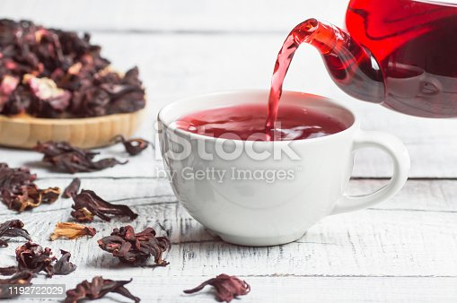 istock White cup of healthy hibiscus tea pouring from the teapot with dried hibiscus flowers on white wooden background, winter hot drink concept for cold and flu 1192722029