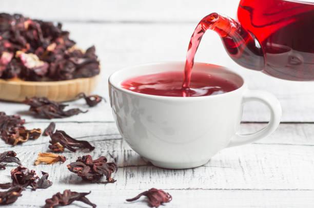copo branco do chá saudável do hibisco que derrama do teapot com flores secas do hibisco no fundo de madeira branco, conceito quente da bebida do inverno para o frio e a gripe - chá bebida quente - fotografias e filmes do acervo