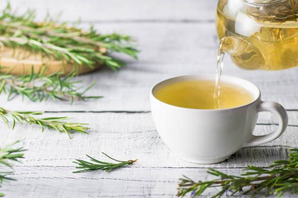 copo branco do chá de rosemary saudável que derrama do teapot com grupo fresco do rosemary no fundo rústico de madeira branco, conceito quente da bebida à base de plantas do inverno, rosmarinus do salvia - chá bebida quente - fotografias e filmes do acervo