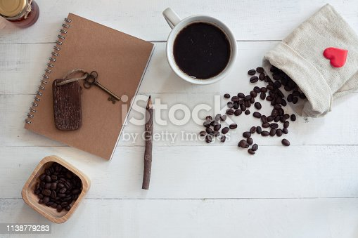 istock White cup of hot black coffee with fresh bubble on book stack decorated with pencil and vintage key on white wooden background, copy space 1138779283