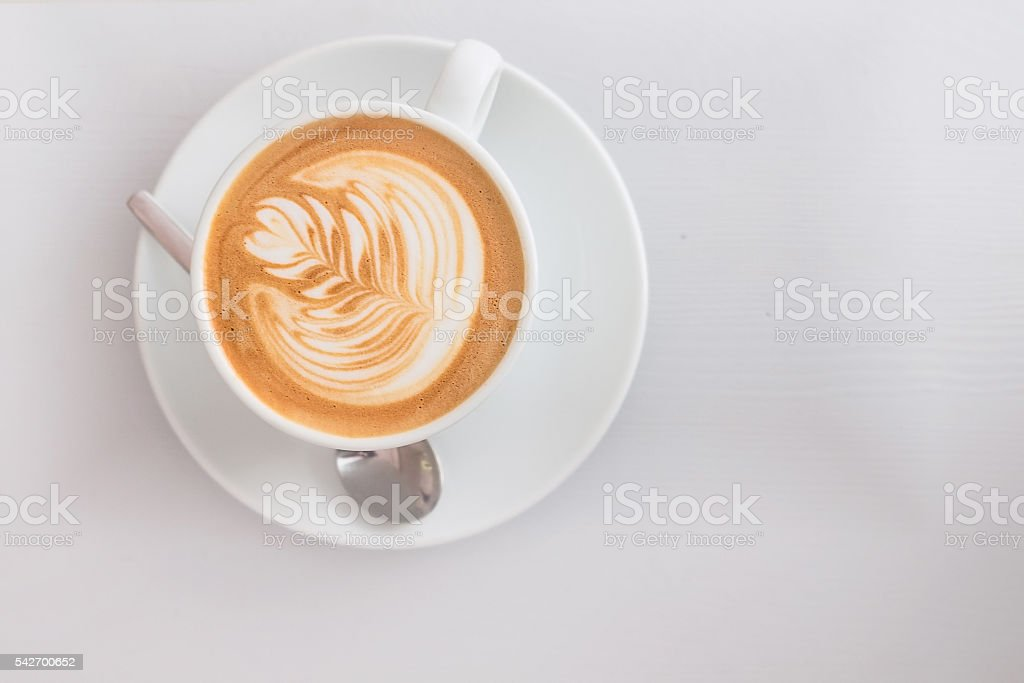 White cup of hot cappuccino art coffee on wooden table stock photo