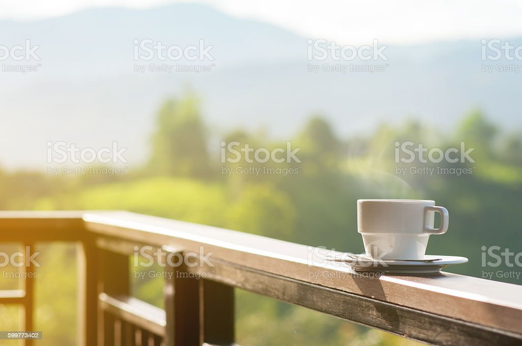 White cup of hot coffee with natural and mountains. - foto de acervo