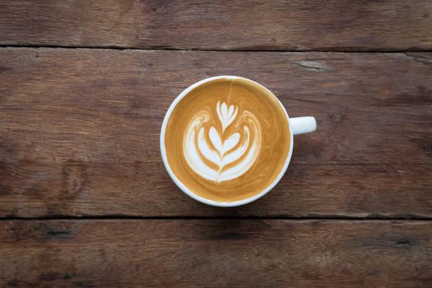 eine weiße tasse heiß und latte art kaffee auf dem holztisch im coffee-shop - cappuccino stock-fotos und bilder