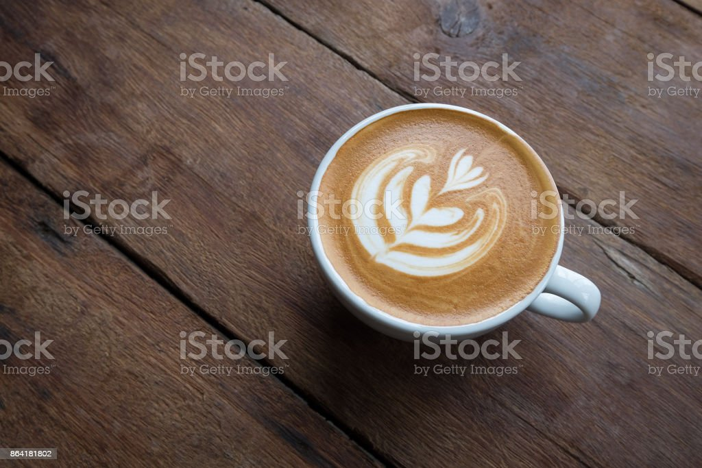 A white cup of hot latte art coffee on the wooden table in coffee shop royalty-free stock photo