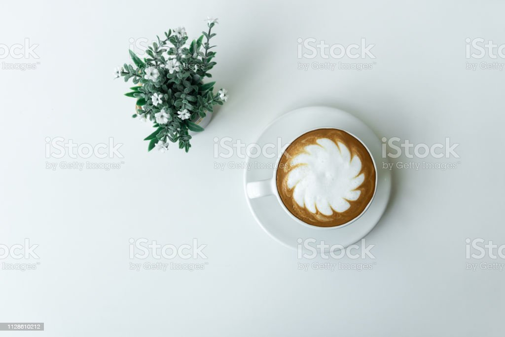 White cup of hot Latte art coffee with Flower Pot on white table