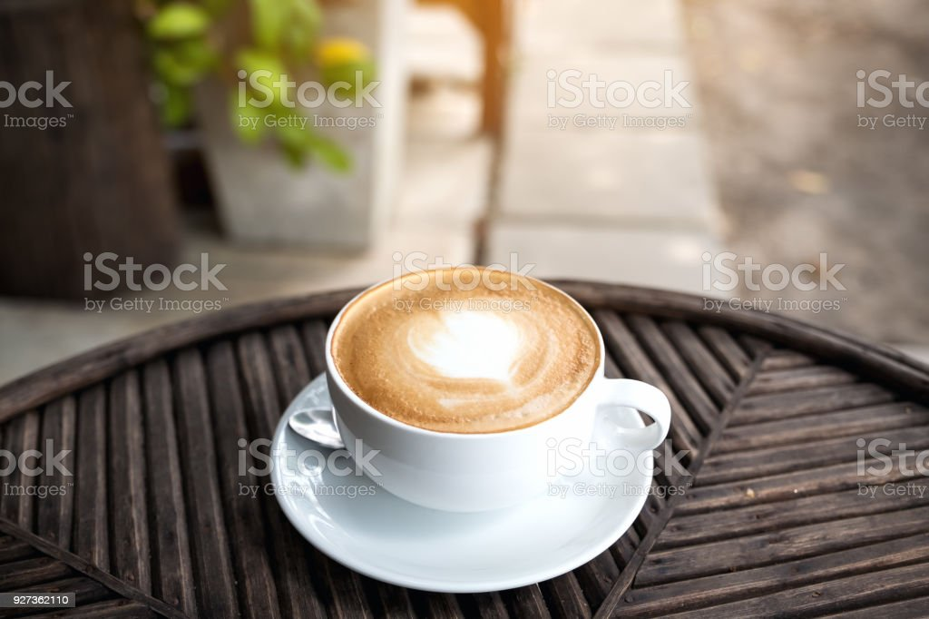A white cup of hot latte coffee with a heart latte art on vintage wooden table with blur green nature background - Royalty-free Art Stock Photo
