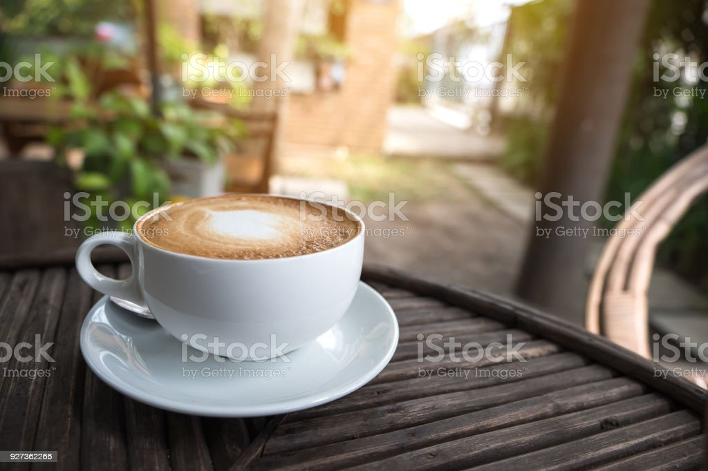 A white cup of hot latte coffee with a heart latte art on vintage wooden table with blur green nature background - Royalty-free Breakfast Stock Photo
