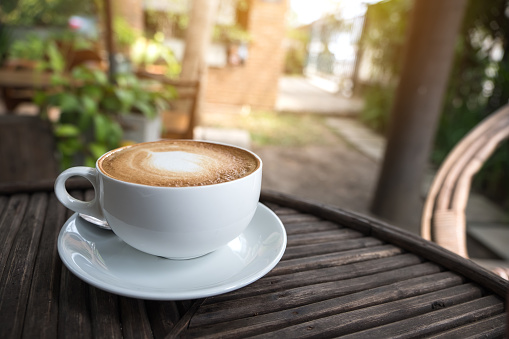 A White Cup Of Hot Latte Coffee With A Heart Latte Art On Vintage Wooden Table With Blur Green Nature Background Stock Photo - Download Image Now