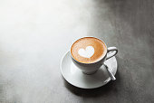White cup of tasty cappucino with love art latte. Valentine's day concept. Concrete grey backdrop. Copy space