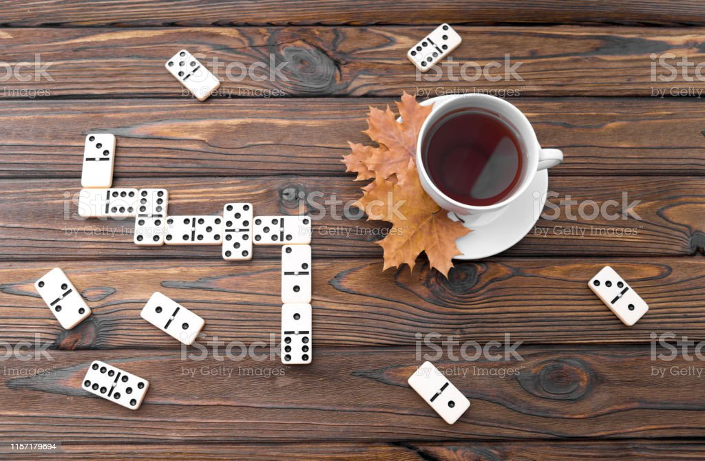 White cup of tea, maple leaves, domino game on a wooden background