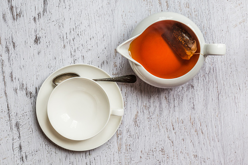 istock White cup of tea with kettle, top view point 535278181