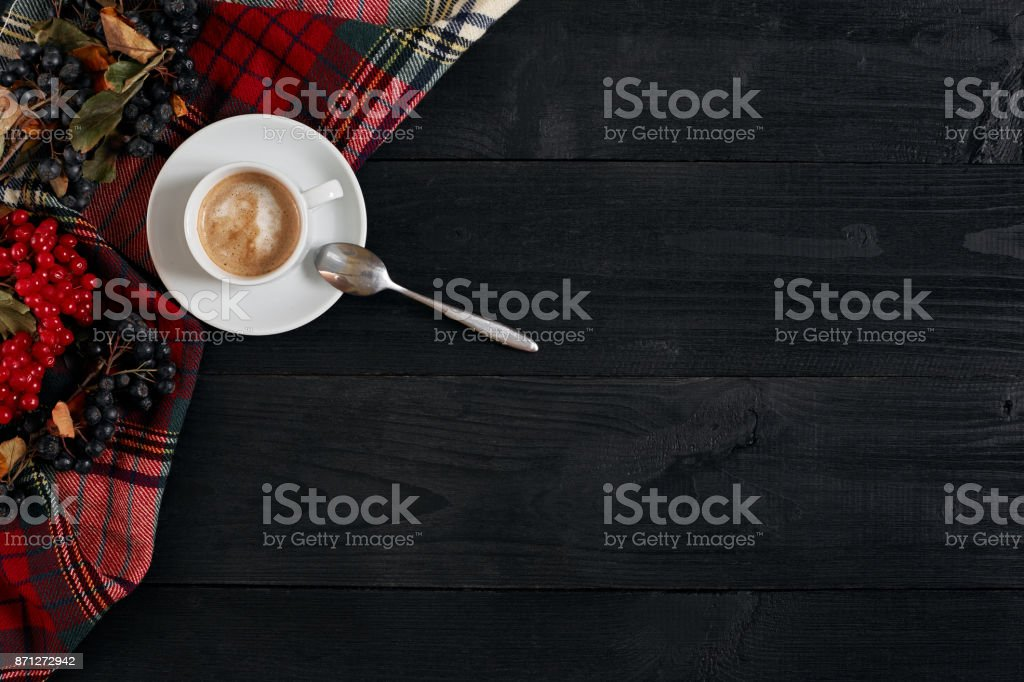 White cup of the coffee and vintage scarf on black wooden background stock photo