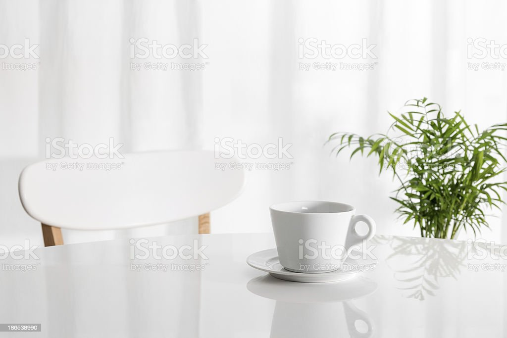 White cup on the kitchen table stock photo