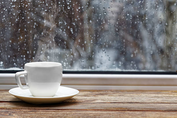 white cup on wooden windowsill - pluie photos et images de collection