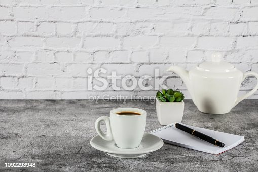 White cup with black coffee and a blank notepad, pen on a gray stone background. Place for text.