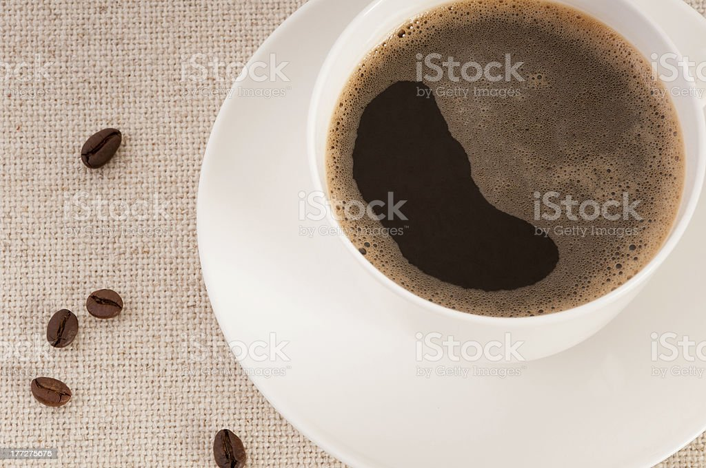 White cup with black coffee and beans on canvas royalty-free stock photo
