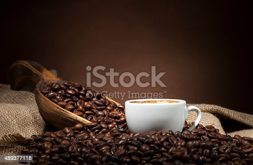 istock White cup with coffee beans on dark background 489377118