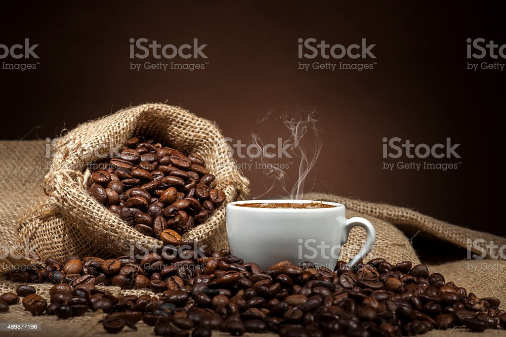 White cup with coffee beans on dark background stock photo