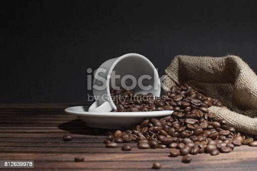 istock White cup with coffee beans on dark background 812639978