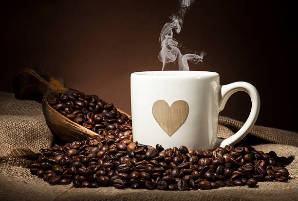 White cup with heart and coffee beans on dark background stock photo