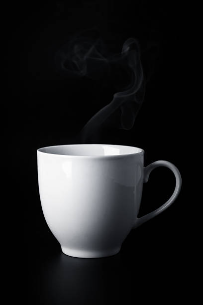 white cup with hot liquid and steam on black stock photo