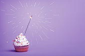 White cupcake with sparkler on light pink background