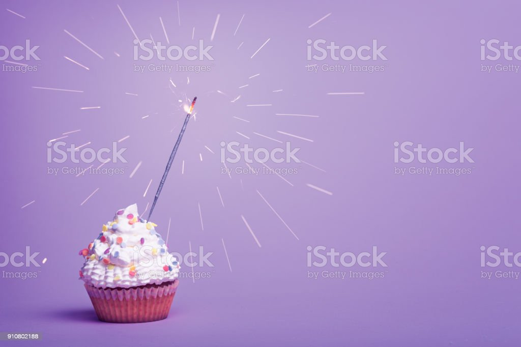 White cupcake with sparkler on light pink background stock photo