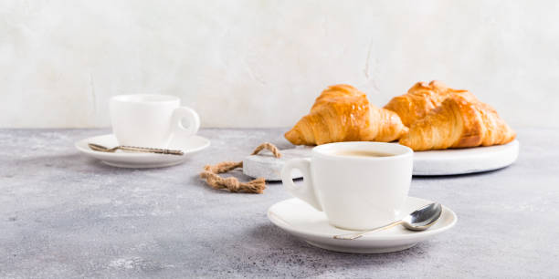 White cups of coffee and croissants stock photo