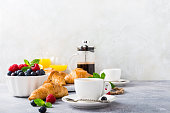 istock White cups of coffee and croissants 676067288